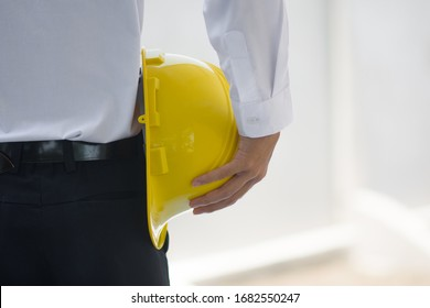 Close up Businessman holding yellow hard hat builder construction estate