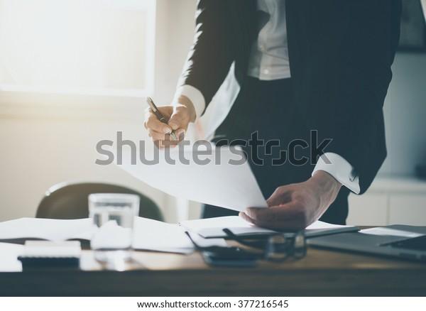 Nahaufnahme eines Geschäftsmanns oder Anwalts-Buchführers, der Dokumente an einem Schreibtisch mit schwarzem und weißem Hemd unterzeichnet