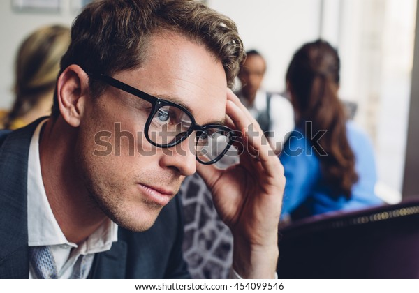 Close up of a businessman looking stressed. He has his hand on his head and there are other people in the background.