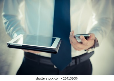 close up businessman man hand using tablet and smart phone device outdoor