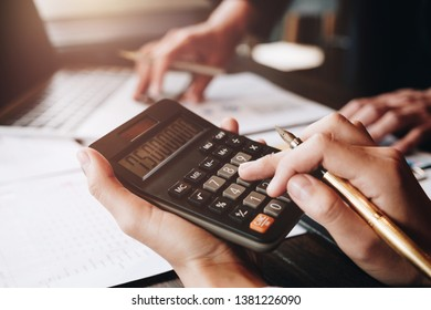 Close up Businessman and partner using calculator and laptop for calaulating finance, tax, accounting, statistics and analytic research concept