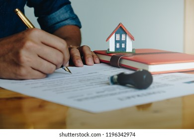Close up of Businessman pointing and signing agreement for buying house. Bank manager concept.