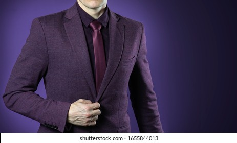 Close up of businessman in purple suit confident on dark blue background.