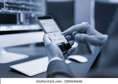 Close up of a businessman reviewing data on smart phone in corporate office. Focus on mobile device. Blue toned black and white image.