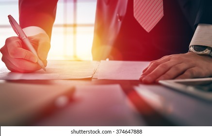 Close up businessman signing documents.