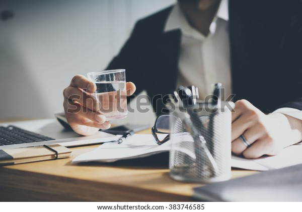 Close up of businessman sitting behind a desk and holding a glass of water while working at his office with laptop