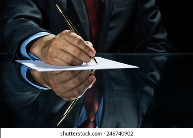 Close up of businessman sitting at table and signing document