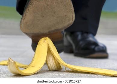 Close up businessman stepping on banana skin peel