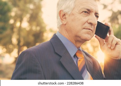 Close up of a businessman talking by phone with glowing sunshine with retro filter effect