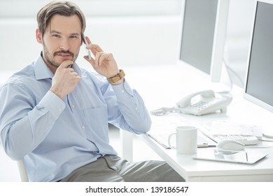 Close up of businessman talking mobile phone at the desk