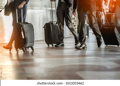 Close up of businessman team carrying suitcase while walking through a passenger boarding bridge.people and traveling luggage walking in airport terminal building