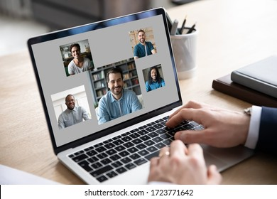 Close up of businessman use modern laptop have webcam conference or briefing with diverse colleagues, make employee talk brainstorm on video call on computer with coworkers or team, online meeting
