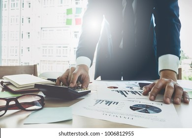 Close up Businessman using calculator for do math finance on wooden desk in office and business working background, tax, accounting, statistics and analytic research concept