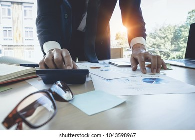Close up Businessman using calculator for do math finance on wooden desk in office, tax, accounting, statistics and analytic research concept