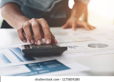 Close up Businessman using calculator and laptop for do math finance on wooden desk in office and business working background, tax, accounting, statistics and analytic research concept