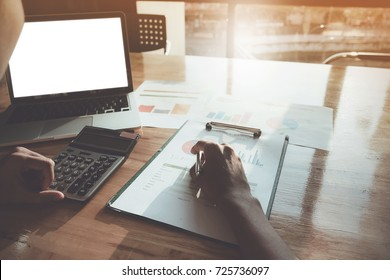 Close up Businessman using calculator and laptop for do math finance on wooden desk in office, tax, accounting, statistics and analytic research concept
