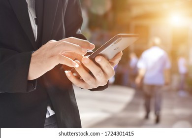 Close up of businessman using a cell phone. Young business executive with mobile phone .