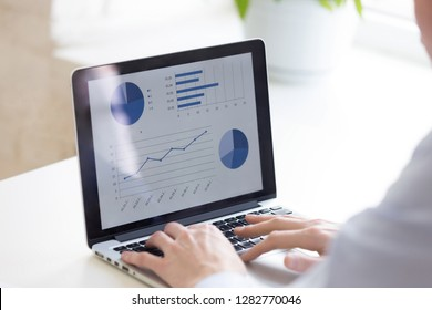 Close up businessman using laptop, analyze business statistics, look at screen, presentation with graphs and diagrams, writing financial report, project management, accounting, market research