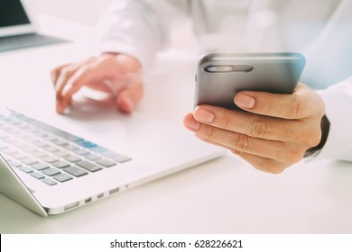 close up of businessman using mobile phone and laptop computer on white desk in modern office