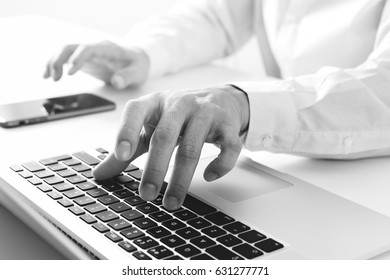 close up of businessman using mobile phone and laptop computer on white desk in modern office,black and white