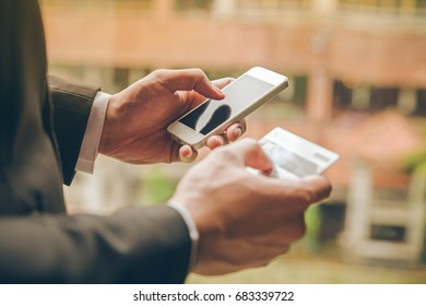 Close up businessman using smart phone and holding credit card with online payment concept.