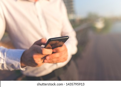 Close up of businessman using smartphone outdoors.