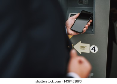 Close up of businessman using smartphone while making payment in the parking. Focus on mobile phone