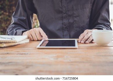 Close up businessman using tablet working in coffee shop.