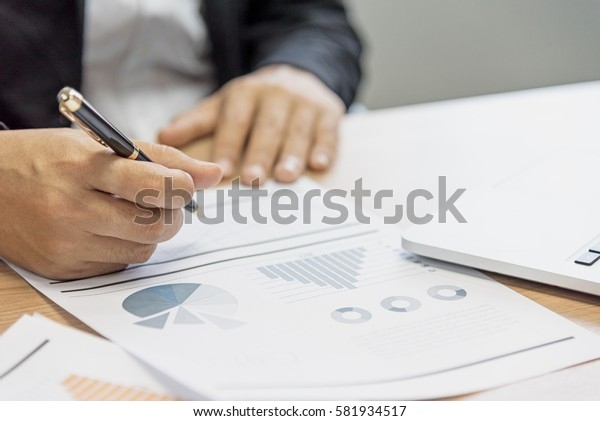 Close up of businessman working in his office with smart phone,document and laptop in business concept