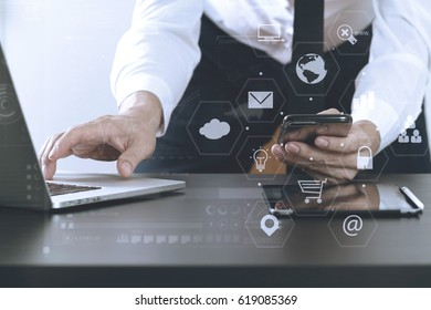 close up of businessman working with mobile phone and laptop and digital tablet computer in modern office with virtual icon diagram