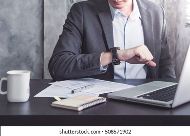 Close up of Businessman working on the desk and checking time on his wrist watch.