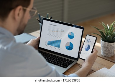 Close up businessman working with statistics, looking at laptop and phone screens with graphs and diagrams, synchronizing electronic devices, checking financial report presentation, sitting at desk