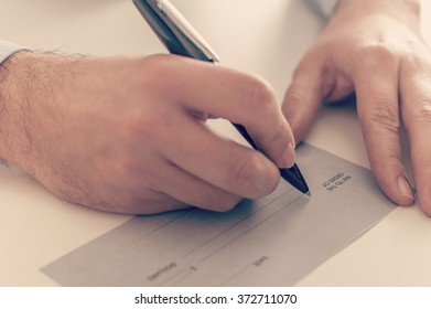 Close up of a businessman writing a payment check