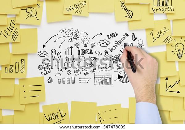 Cerrar la mano de un hombre de negocios con camiseta azul dibujando iconos de ideas de negocios en una pizarra blanca cubierta de notas pegajosas.