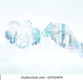 Close up of businessman's hand holding abstract cogs on city background. Success concept. Double exposure