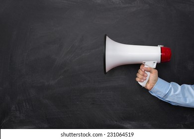Close up of businessman's hand holding megaphone over chalkboard background with copy space