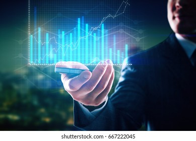 Close up of businessman's hand holding smartphone with digital business chart on blurry night city background. Fintech concept