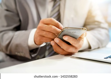 Close up of businessman's hands using stylus pen on cellphone