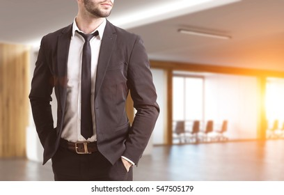 Close up of a businessman's torso. He is wearing a suit and standing with his hands in pockets. There is a conference room in the background. 3d rendering. Toned image