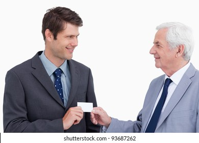 Close up of businessmen exchanging business card against a white background