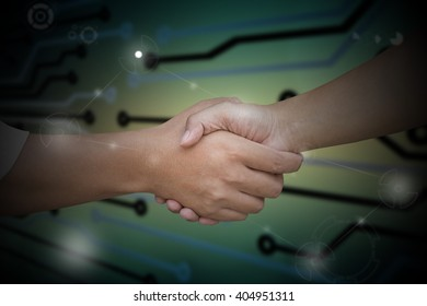 Close up of businessmen shaking hands on abstract technology background for computer graphic website internet and business, finishing up a meeting.
