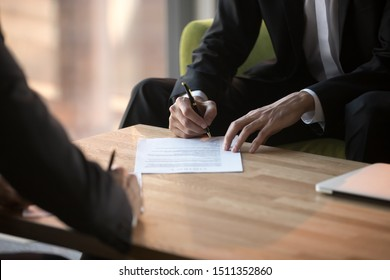 Close up businessmen signing partnership agreement, business partners making legal deal, putting signature on official paper document, taking loan or purchase property, male hands holding writing pen