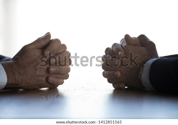 Close up of businessmen sit at table with clasped hands having dispute or discussion, serious men opponents talk negotiating at desk with arms clenched, engaged in dialogue. Rivalry concept
