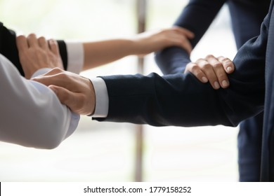 Close up businesspeople connected arms standing side by side shoulder by shoulder show business protection, feel unity, corporate spirit save, strength of four, act together towards common aim concept