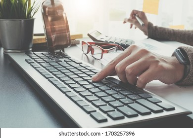Close up of businesswoman or accountant hand holding pencil working on calculator to calculate financial data report, accountancy document and laptop computer at office, business concept