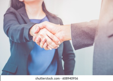 Close up businesswoman and businessman shaking hands Business partnership concept,Filter color effect