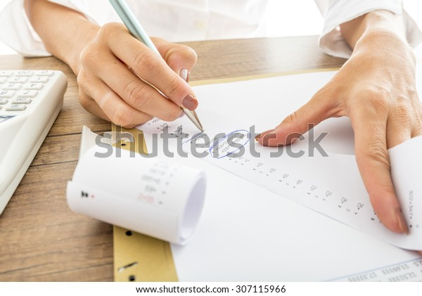 Close up Businesswoman Calculating Expenses on Printed Receipts at her Desk with Calculator on her Side.