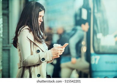 Close up of businesswoman checking email via mobile phone and holding a coffee cup.