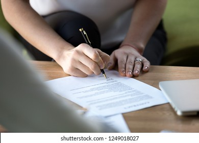 Close up of businesswoman hand holding ballpoint after checking official paper ready to sign agreement. Female affirming contract with signature. Concept of collaboration, trust and successful deal
