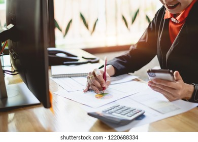 Close up Businesswoman hand holding pen and pointing at financial paperwork.